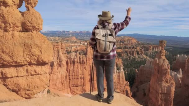 A Hiker Woman Raises Her Hand, Standing Over The Edge Of The Bryce Canyon