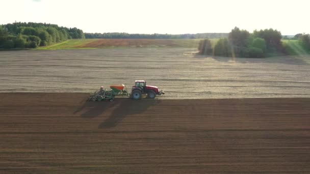 Tractor Plowing Field Or Planting Grains Against Sunshine At Sunset Aerial View