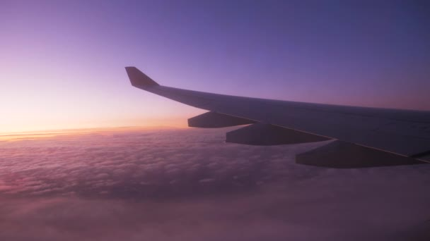 View Of Wing Of Airplane Flying Altitude Over Clouds With Romantic Sunset Sky