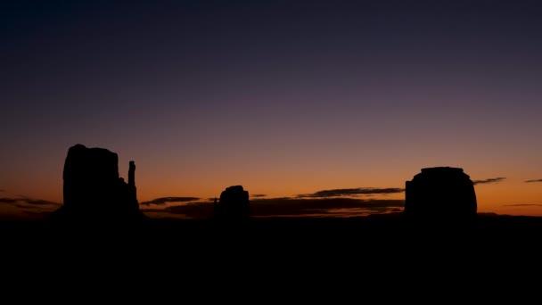 Timelapse při východu slunce v Monument Valley s vysokou černou siluetou Rock Buttes
