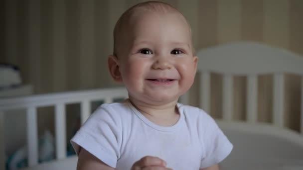 Portrét dítěte při pohledu na kameru usmívající se na pozadí kolébky v pokoji