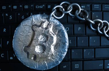 Bitcoin chain in blue. Real coin of crypto currency joined by metal chain is on a computer keyboard
