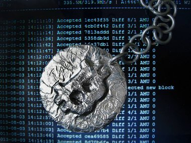 Bitcoin chain. Real coin of crypto currency joined by metal chain is on a mining computer screen