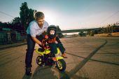 Fotografia Trainer insegna piccoli bikers per fare acrobazie su una moto