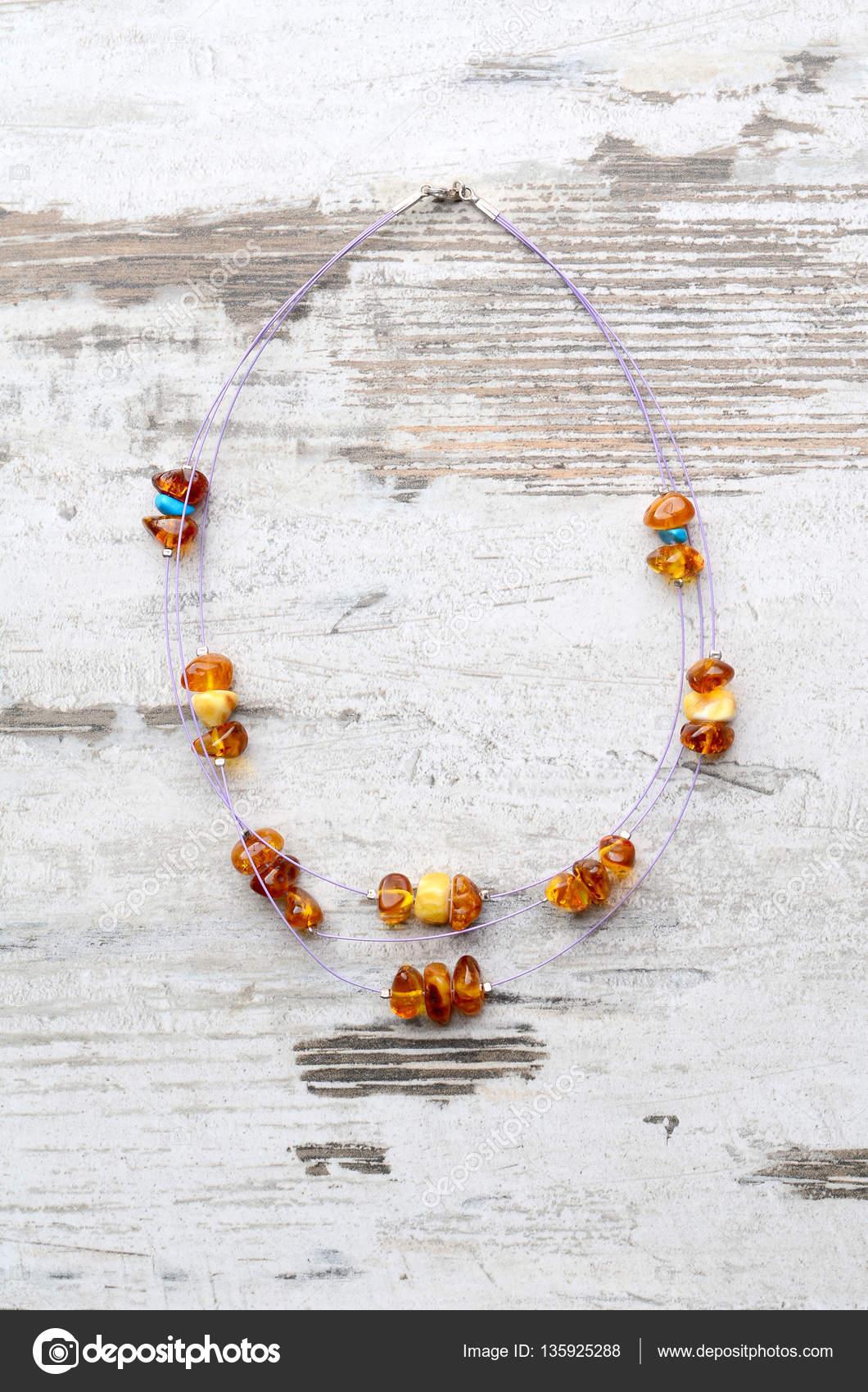 2a07e6e57 Zářivě oranžové jantarový náhrdelník surového korálků náhrdelník z Jantarové  korálky jantar korálky string na staré šedé dřevěné pozadí — Fotografie od  ...