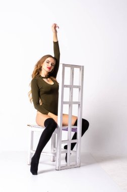 Young sexy woman sitting on chair.