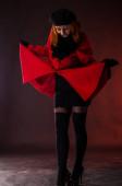 Model in rotem Mantel blickt lächelnd auf ihr Gesicht