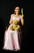 Nádherná zrzka žena v roztomilé růžové šaty držení hračka medvěd a nůž v ruce