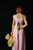 Gorgeous redhead woman in cute pink dress holding toy bear and knife in hands