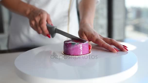 Eine weibliche Hand schneidet eine rosa Torte auf einem weißen Tisch. Moussekuchen. leckeres Dessert