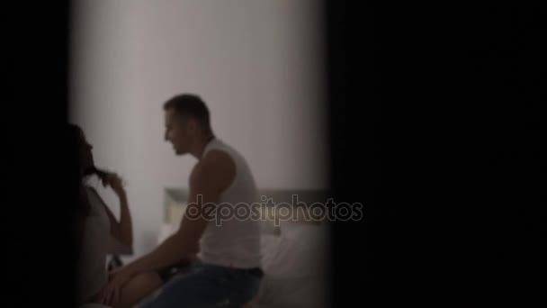 Brunette meisje en jongen in de ochtend in bed hand in hand