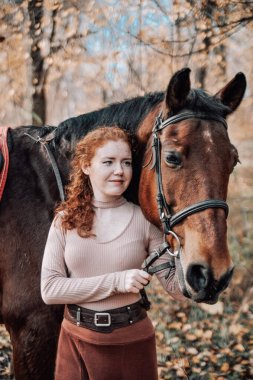 Portrait of beautiful red haired woman with horse outdoors.