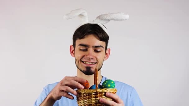 Húsvéti tojás. Egy fiú fülekkel és húsvéti tojással a kezében. Húsvét. Fehér alapon