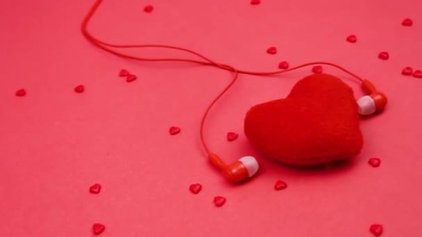 Červené srdce a červená sluchátka. srdce na červeném pozadí. Srdce a sluchátka. Poslouchej srdce.