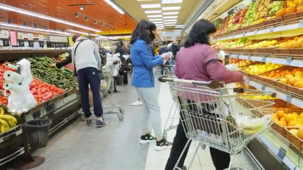 Supermarket. Obchod s potravinami. Obchod s ovocem a zeleninou. Lidé si vyberou produkt. COVID-19