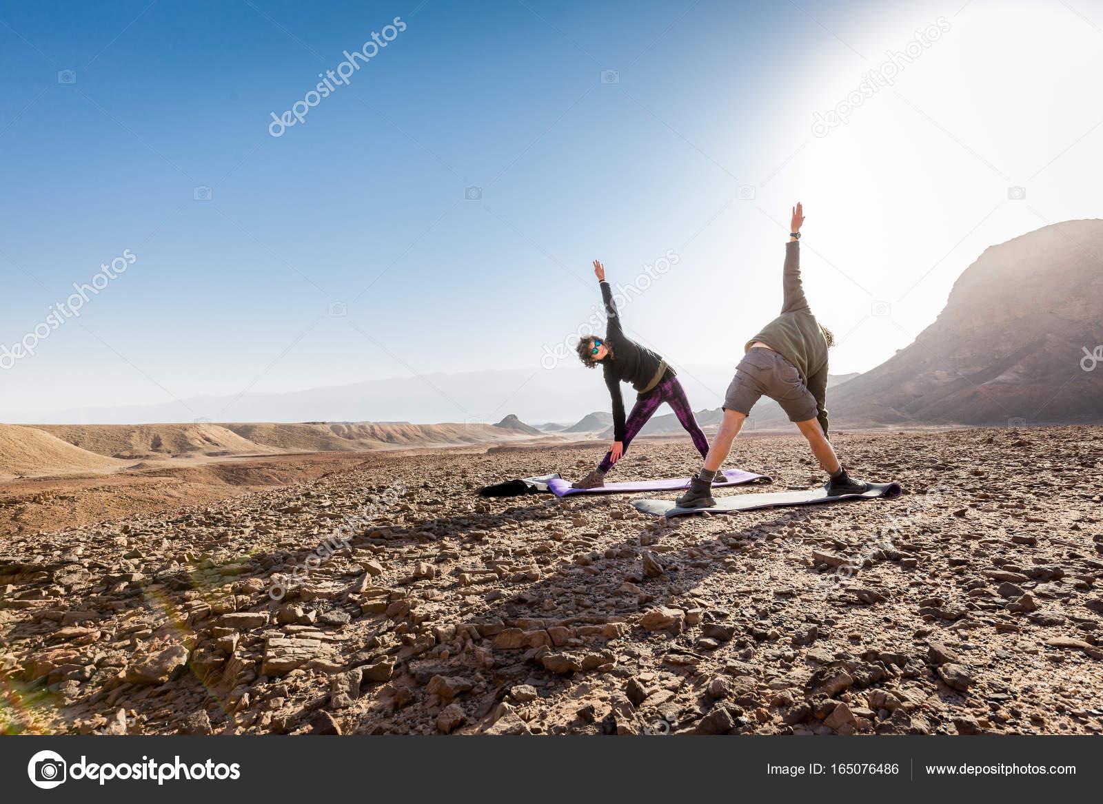 Young couple training yoga exercise asana desert morning