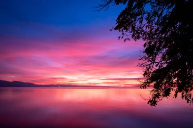 dark violet clouds with orange sun light and pink light in wonderful twilight sky. Silhouettes of trees on the background of the lake Bodensee in Lindau
