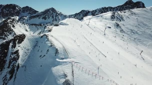 Aerial view smooth movement along the ski slopes in the ski resort of Grandvalira in Andorra. Magnificent snowy mountains and blue sky. Winter landscape