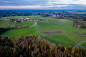 Fotografie Luftaufnahme Herbstlandschaft in Bayern bei Miesbach. Straße in die Ferne und die Gipfel der Alpen am Horizont. Wolken Himmel, gelbe Bäume und grünes Feld
