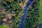 Fotografie Blick von oben auf den Herbstwald und einen kleinen Fluss, der durch den Wald fließt