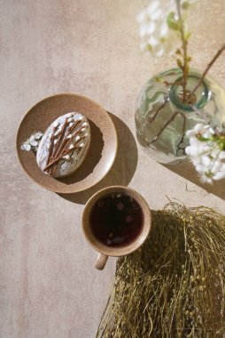 A cup of tea with camomile and berries, icing cookie on a plate, dried chamomile, flowering cherry branch in glass vase on the grey texture background. Copy of space. Top view