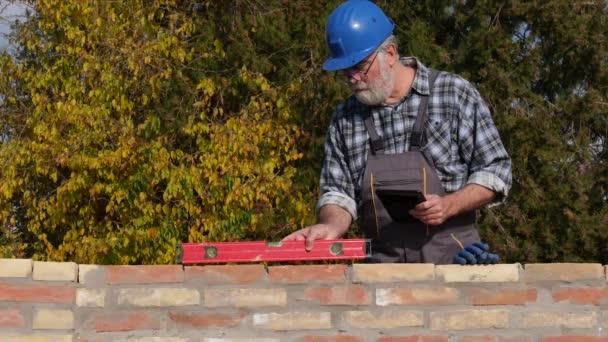 Munkavállaló vagy mérnök ellenőrző téglafal szintű eszköz és a tablet használata