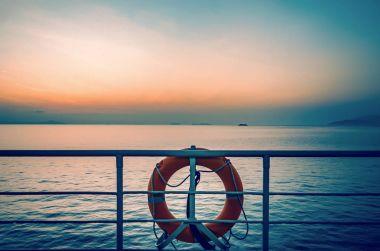 sunset on sea and orange lifebuoy at railing of cruise ship deck