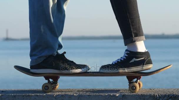 Zwei Beinpaare sind auf dem Skateboard, küssen