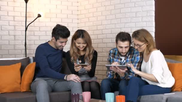 multinationale Unternehmen sitzen auf der Couch und sehen Video auf Tablet und Smartphone 50 fps
