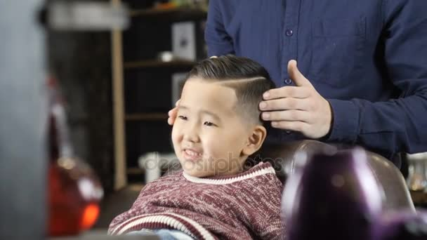 Barber In Black Gloves Makes A Hairstyle For An Asian Child Puts A