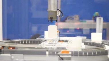 Mechanical hand moves a plastic bottle, a conveyor, a conveyor belt, a factory, a production