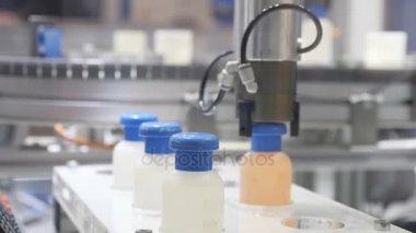 Mechanical hand moves plastic bottles, conveyor belt, conveyor belt, factory, production