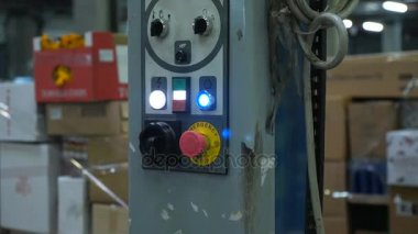 Gloved hand presses the power button on a special machine in the warehouse
