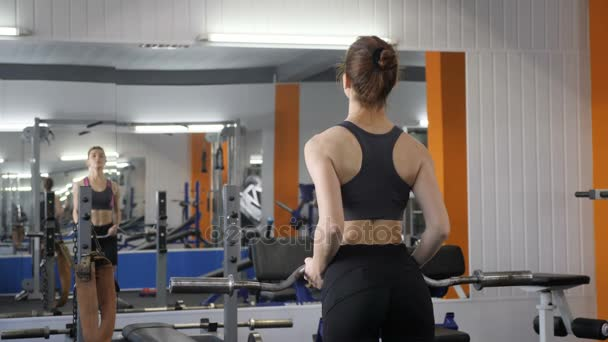 Young beautiful sporty girl lifting barbell bar in gym, pumping biceps. 60 fps