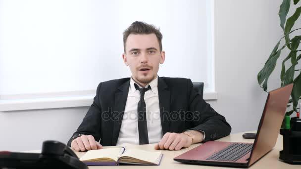 junger Geschäftsmann im Anzug sitzt im Büro und zeigt mit dem Finger nach oben, hat eine Idee 60 fps