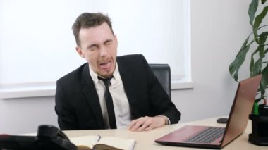 Young businessman in suit sitting in office and Sticks Tongue Out, Makes Funny Faces 60 fps