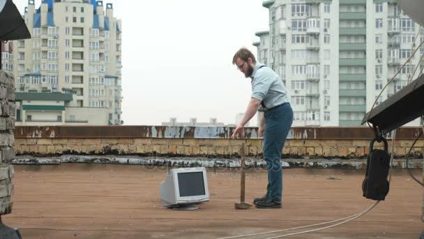 Mladý silák rozbije monitor s kladivem na střeše. Kladivo, bat, násilí, nenávist, anarchie, ničení. 60 snímků za sekundu