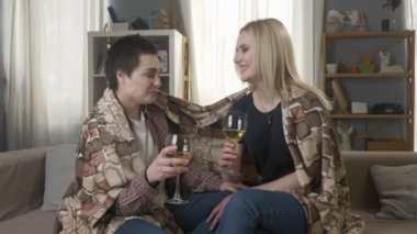 Two young, beautiful girls are sitting on the couch wrapping with warm plaid blanket, drinking wine and laughing 60 fps