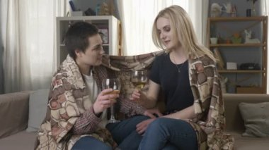 Two young, beautiful girls are sitting on the couch wrapping with warm plaid blanket, drinking wine and speaking 60 fps