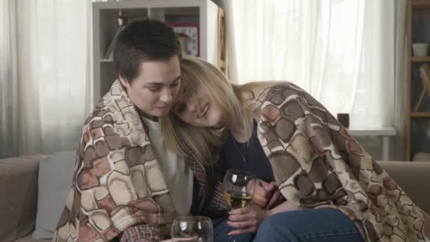 Two young, beautiful girls are sitting on the couch wrapping with warm plaid blanket, drinking wine and hugging, cuddle. 60 fps