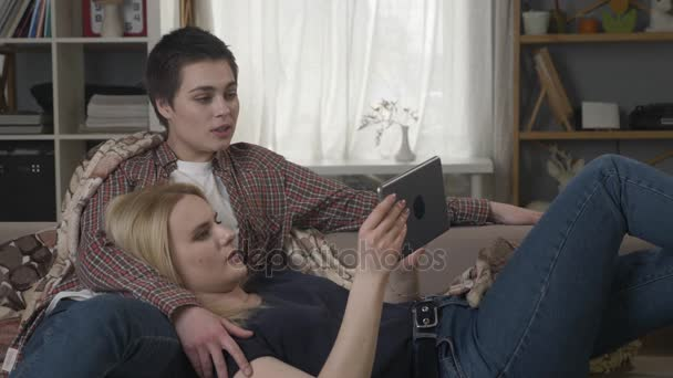 Lesbian couple is resting on the couch, using tablet computer, scrolling photos on tablet, holding hands, smiling, talking, family idyll, love 60 fps
