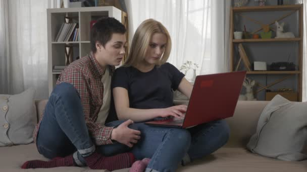 Two young lesbian girls are sitting on the couch, using a computer, scrolling the internet, shopping online, the blonde maliciously closes the laptop, quarrel 60 fps