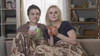 Two young lesbian girls are sitting on the couch, covered with a warm blanket, holding cups in their hands, drinking dark tea, coffee, cuddling 60 fps
