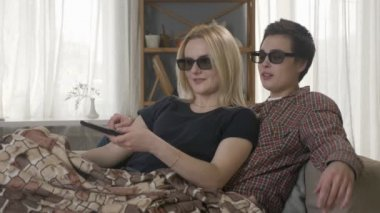 Two young lesbian girls are sitting on the couch, covered in a warm blanket, watching the 3d film, using the remote control, laughing. 60 fps