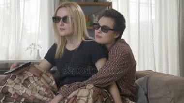 Two young lesbian girls are sitting on the couch, covered in a warm blanket, watching the 3d film, using the remote control, shocked, surprised 60 fps