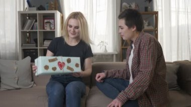 Two young lesbian girls are sitting on the couch, a girl with blond hair is pleased with the gift, hugs 60 fps