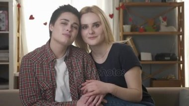 Two young lesbian girls sitting on the couch, looking at the camera, holding hands, hugging, cuddles, love, care, family idyll 60 fps