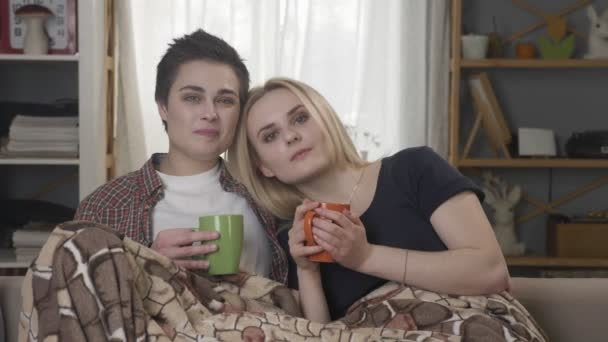 Two young lesbian girls are sitting on the couch, covered with a warm blanket, holding cups in their hands, cuddling, looking at the camera 60 fps