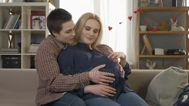 Two young lesbian girls sitting on the couch, pregnant blonde caresses the belly, waiting for the babys appearance, coziness, love, happiness. 60 fps