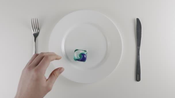 A mans ruky bere mycí prášek pod z talíře, pracích prostředků pod. Příprava k jídlu kapsle s detergentem, prací prášek lusky výzvu, internetové meme. 60 snímků za sekundu
